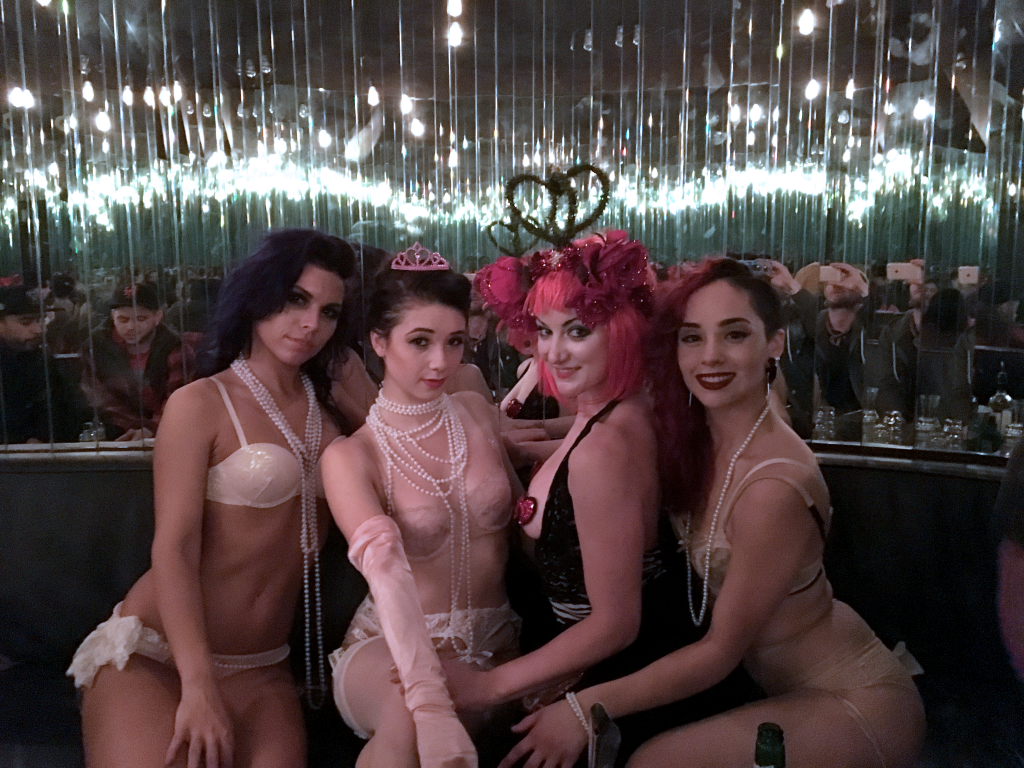 Three beautiful girls surrounding the Queen of Hearts in a mirrored VIP room