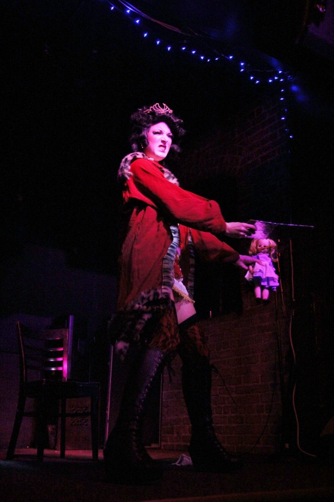 Party Girl Pearl performs onstage as the Queen of Hearts, beheading an Alice in Wonderland doll